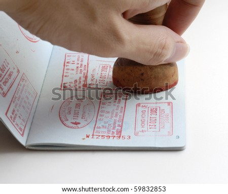 It is a chinese passport for enter HongKong, A hand is taking a stamp. Isolated