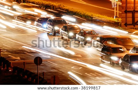 It is a cityscape of cars in the road with yellow blured light.
