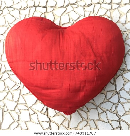 It is a cute red heart shape os cushion on a white mosaic floor. #748311709