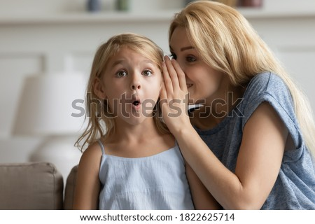 It is a great unknown. Smiling adult mom telling cute story as big mystery on ear of surprised little daughter, creative young nanny finding way to heart of small preschool child sharing funny secret Photo stock ©