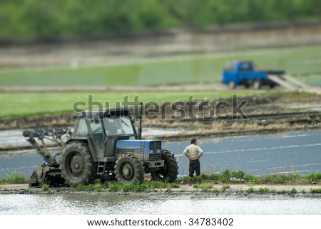 It is a power tiller with truck on the farm land.