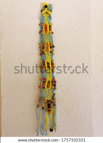 It is a wall ornament made of colored threads and beads. Stok fotoğraf ©