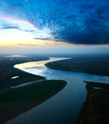 It is aerial view the great river during twilight. On the river is calm now. Beautiful clouds are reflected in quiet water.