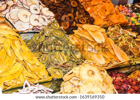 It is an Arabian market. Merchants sell dried fruits. dried fruits are in the wicker baskets. it is a lot of types of dried fruits with plates. Candied kiwi, apricot, apple, pineapple, dried fig, date