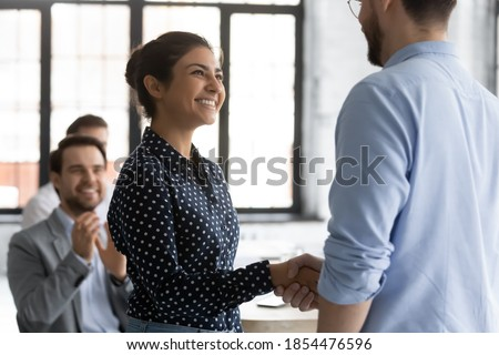 It is an honor to me. Glad smiling young lady corporate worker of indian ethnicity getting recognition acknowledgement of ceo, handshaking higher executive on briefing conference, being hired promoted Stockfoto ©