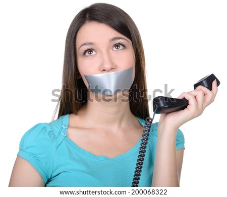 It is better to be silent. Upset girl with self-adhesive tape over her mouth, trying to talk on the phone Stock photo ©