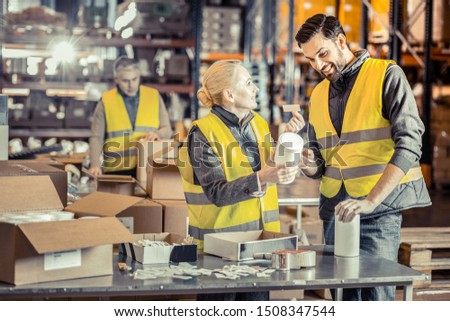 It is correct. Pleased blonde woman keeping smile on her face while consulting her worker