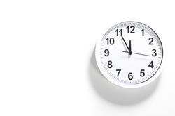 It is five to twelve, the clock is ticking. White Watch shows the time 5 before 12. Close up to a wall clock, with five minutes to twelve o'clock. Time is running out. White background with copy space
