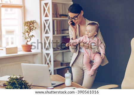 It is not easy to be a working mom! Young beautiful businesswoman talking on mobile phone and looking at laptop while standing with her baby girl at her working place #390561016