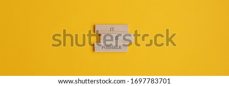 It is possible sign on stacked wooden pegs placed over yellow background. Wide view image with copy space.  Stockfoto ©