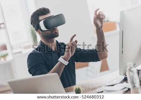 Photo of It is so real! Handsome young man in VR headset gesturing and smiling while sitting in creative office