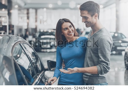 It is the one car I want! Beautiful young couple standing at the dealership choosing the car to buy