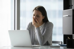 It makes me sleepy. Bored unmotivated young woman worker cannot resist yawn sitting by laptop in office doing dull monotonous task, tired millennial female employee works online after sleepless night