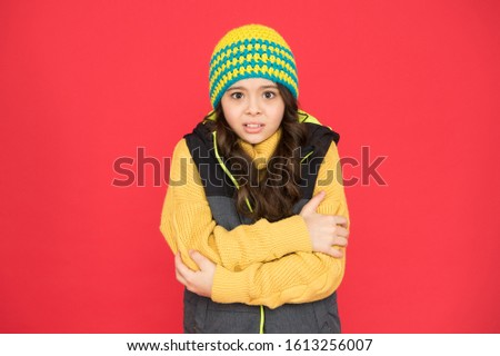 It might be too cold to trek outside. Little child feel cold red background. Small girl shiver in cold weather wear. Chilly season. Autumn or winter. Cold and chill. Coldness. Fashion and style.