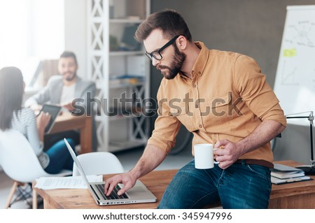 IT professional at work. Confident young man working on laptop while his colleagues talking in the background