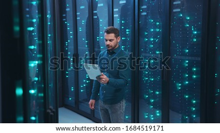 IT professional with digital tablet monitoring system performance of database network servers working on rack in high tech data center. Webhosting, cloud computing.