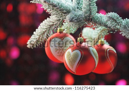 It's Christmas, red balls hangs from a frosted pine tree - stock photo