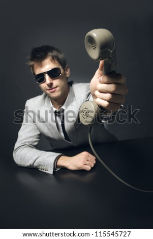 It's for you! Businessman holding retro telephone