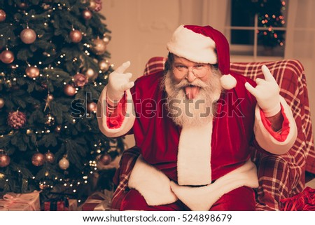 It\'s party! Cool Santa Claus showing tongue out and gesturing with fingers rock-and-roll near christmas tree at home