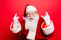 It's party time! Holly jolly swag x mas and noel!  Cool funny playful naughty grandfather with sticking tongue, comic grimace, fooling around isolated on red background, shows rock gesture