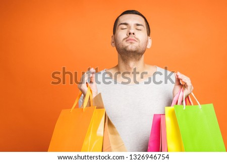 It's shopping time! Happy young man with colorful paper bags isolated on orange background.