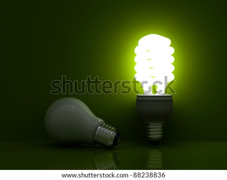 It's time for energy saving light bulb, Glowing compact fluorescent light bulb standing near unlit incandescent light bulb on green background