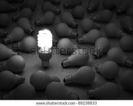 It's time for energy saving light bulb, one glowing compact fluorescent light bulb standing out from the unlit incandescent bulbs