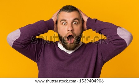 It's unbelievable. Surprised stunned emotional man with hands on his head, being shocked to see sales prices. Guy can't believe in shocking news, panorama, yellow background