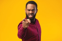It's Your fault. Angry african american man pointing finger at camera, blaming you, yellow studio background