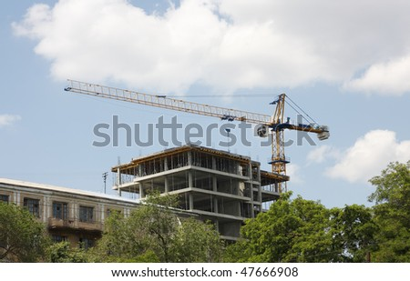 It shows construction crane and unfinished house on the skyline