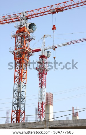 It shows two construction cranes and unfinished house on the skyline