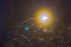 It snows at night against the background of a lantern illuminating the street.