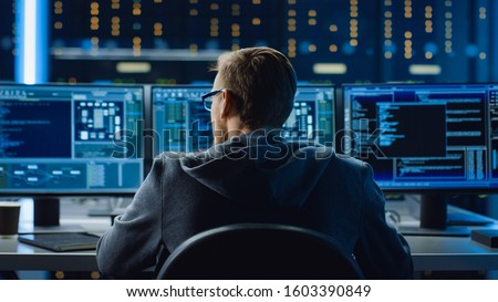 IT Specialist Working on Personal Computer with Monitors Showing Coding Language Program. Technical Room of Data Center with Server Rack.