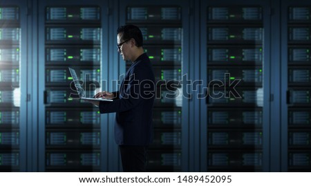 IT Technician in suit works on laptop working in server room .