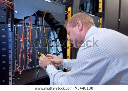 IT technician working on network servers and cables.