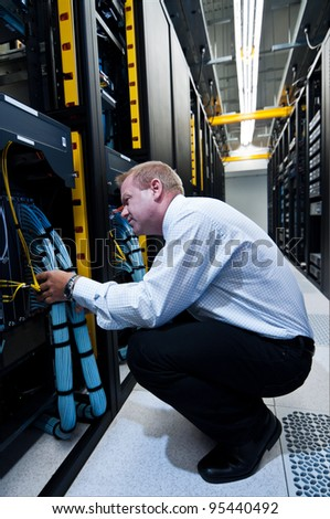 IT technician working on network servers and cables