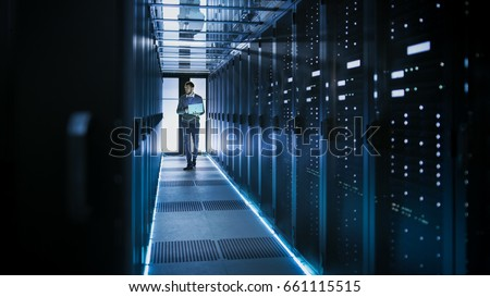 IT Technician Works on Laptop in Big Data Center full of Rack Servers. He Runs Diagnostics and Maintenance, Sets System Up. #661115515