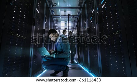 IT Technician Works on Laptop in Big Data Center full of Rack Servers. Multiple People Works at Data Center at the same time.