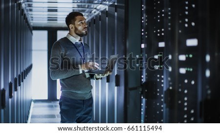 IT Technician Works on Laptop next to a Server Cabinet in Big Data Center. He Runs Diagnostics and Maintenance, Sets System Up.