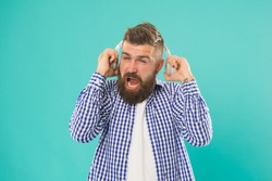it was very loud. elearning with audio book. bearded hipster in checkered shirt. too loud. confused mature man listen music. guy with beard and moustache wear headphones. male express emotions.