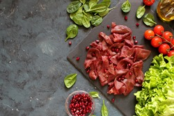 Italian air - dried salted bresaola beef thinly sliced and stone board. Top view. Iron on the food. Diet food. Copy space.
