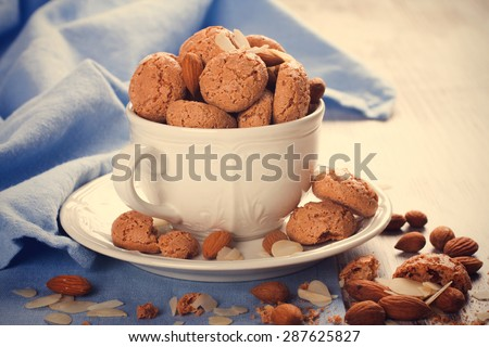 Italian almond cookie amaretti in white coffee cup with almonds on white table with blue napkin, selective focus. retro style toned.