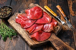 Italian Antipasti Bresaola cured meat beef cut pieces. Dark wooden background. Top view