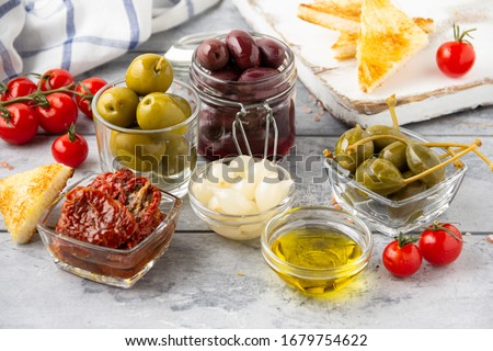 Italian antipasti, olives, capers, sun- dried tomatoes , olive oil, bread (ciabatta, baguette, croutons). Mediterranean assortment of delicious food, wine snacks Stock photo ©