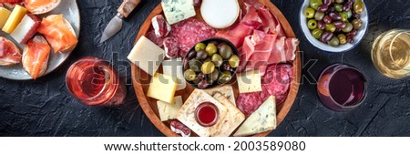 Italian antipasti or Spanish tapas panorama. Gourmet cold meat and cheese platter on a table, shot from the top with wine on a black background. A variety of appetizers Stock photo ©