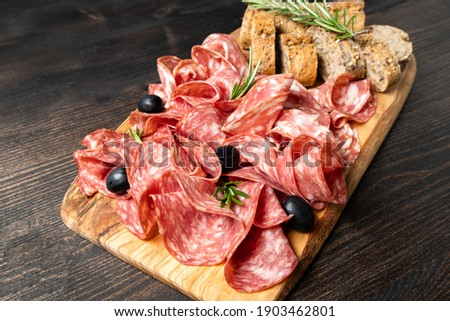 Italian antipasti salami with bread.  with olives and multigrain baguette.  italian food, appetizer for aperitif or salami sandwich. Top view Elegant serving of snacks in the restaurant Stock photo ©