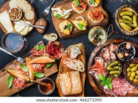 Shutterstock Italian antipasti wine snacks set. Brushettas, cheese variety, Mediterranean olives, pickles, Prosciutto di Parma with melon, salami and wine in glasses over black grunge background, top view