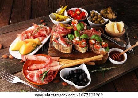 Italian antipasti wine snacks set. Cheese variety, Mediterranean olives, pickles, Prosciutto di Parma, tomatoes, artichokes and wine in glasses #1077107282