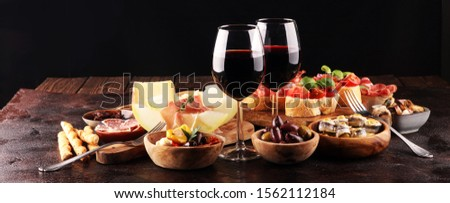 Italian antipasti wine snacks set. Cheese variety, Mediterranean olives, pickles, Prosciutto di Parma, tomatoes, anchovy and wine in glasses over black grunge background Stock photo ©