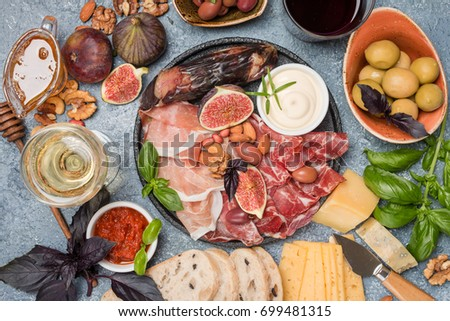Italian antipasti wine snacks set. Cheese variety, nuts, Mediterranean olives, sauces, Prosciutto di Parma or jamon, and wine over gray background, top view #699481315
